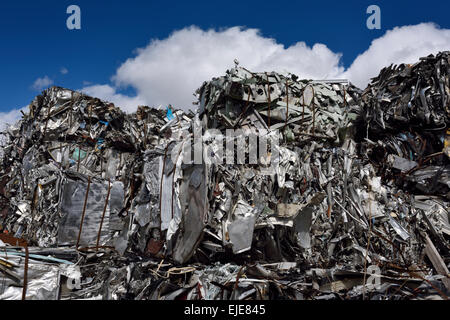 Bales of crushed recycled scrap metal in junkyard with blue sky clouds Toronto - Stock Photo