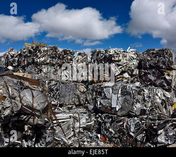 Mountain of crushed recycled scrap metal cubes with blue sky and clouds Toronto - Stock Photo