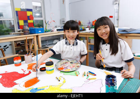 Two little girls painting in the classroom - Stock Photo