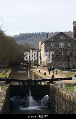 Couple walking along Rochdale canal towpath in Hebden Bridge, West Yorkshire, England, UK - Stock Photo