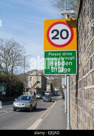 20 mph speed restriction sign with speeding  car, Hebden Bridge, West Yorkshire, England, UK - Stock Photo