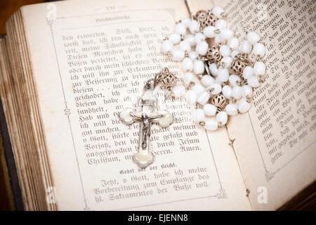 crucifix with silver jesus on opened holy bible with christian psalms, - Stock Photo