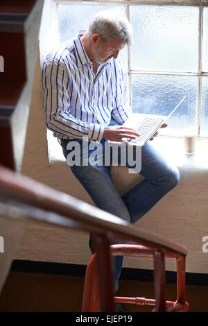 Casually Dressed Businessman Working On Stairs In Office - Stock Photo