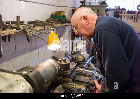 Engineer and vintage car maker working on his lathe in the workshop - Stock Photo