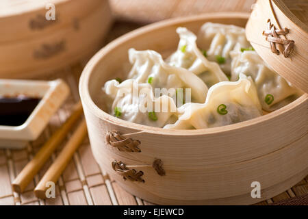 Dim sum with leeks, meat, and green onions in a bamboo steamer. - Stock Photo