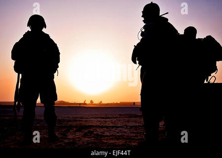 U.S. Army Soldiers wait in the early morning for two UH-60 Black Hawk helicopters to pick them and bring them to - Stock Photo