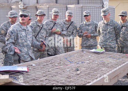 Army 2nd Lt. John Deal, Roughneck platoon leader, explains mission details using a sand table, under the watch of - Stock Photo