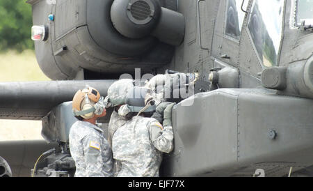 U.S. Soldiers with 2-159th Attack Reconnaissance Battalion, 12th Combat Aviation Brigade, refuel an AH-64D Apache - Stock Photo