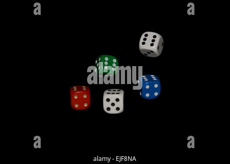 Tumbling dice isolated against a black background - Stock Photo