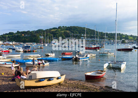 Boats in the harbour and family group on beach at coastal resort of Teignmouth in South Devon, England, UK - Stock Photo
