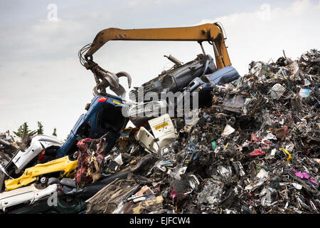 Grab machine moving scrap metal, cars and autos for metal recycling to avoid environmental pollution in England - Stock Photo