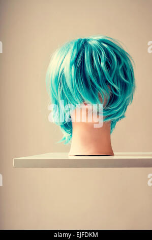 a blue wig in a mannequin head on a white shelf mounted on the wall - Stock Photo