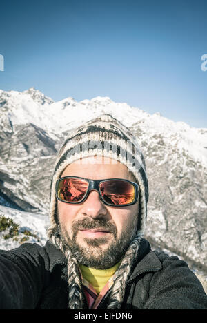 Adult european man with beard, sunglasses and hat, taking selfie on snowy slope with the beautiful snowcapped italian - Stock Photo