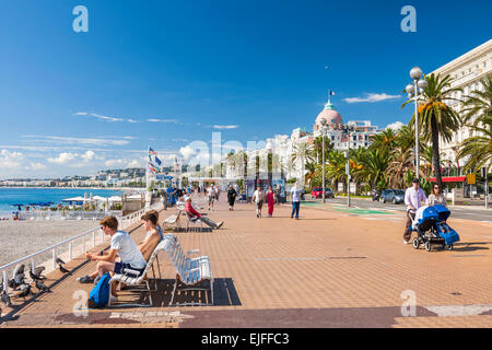NICE, FRANCE - OCTOBER 2, 2014: People enjoying sunny weather and view of Mediterranean sea at English promenade - Stock Photo
