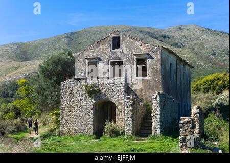 Tourists visiting Skordilis Mansion house ruin in oldest village of Corfu - ancient Old Perithia - Palea Perithea, - Stock Photo