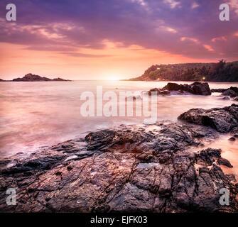Sea with rocks at violet sunset sky in Om beach, Gokarna, Karnataka, India - Stock Photo