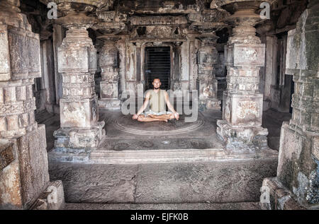 Man doing meditation in ancient temple with carving columns in Hampi, Karnataka, India - Stock Photo