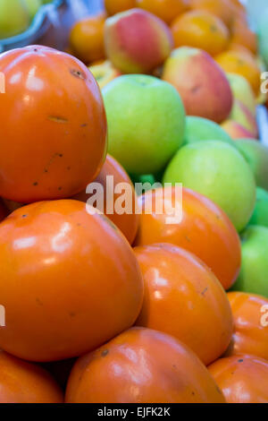 Persimmon fruits on display at a local shopping center and farmers market - Stock Photo