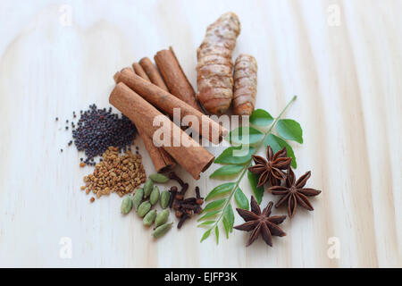 Assorted dried spices including fresh murraya koenigii on a wooden board - Stock Photo