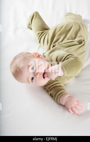 six months age blonde baby green velvet onesie lying on white sheet bed smiling happy face - Stock Photo