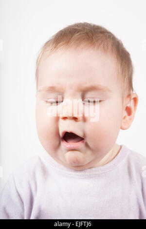 portrait of eight months age blonde lovely cute baby pink velvet onesie disgusted or sneeze face isolated on white - Stock Photo