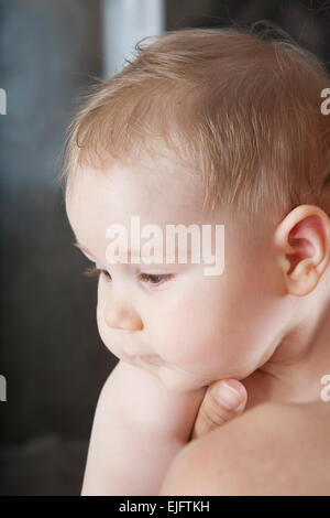 portrait of eight months age blonde lovely cute baby face in mother hands - Stock Photo