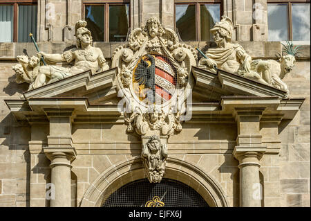Small Nuremberg city coat of arms and allegorical figures on the pediment from the right portal, Old City Hall - Stock Photo