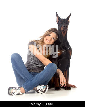 Young woman with black dobermann dog, isolated on white - Stock Photo