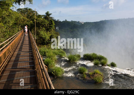 Argentina, Iguazu Falls, tourists on walkway above water flowing over waterfalls - Stock Photo