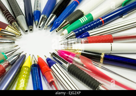 Ballpoint pens and mechanical pencils of various shapes and colors with their tip oriented inwards, forming a circle - Stock Photo