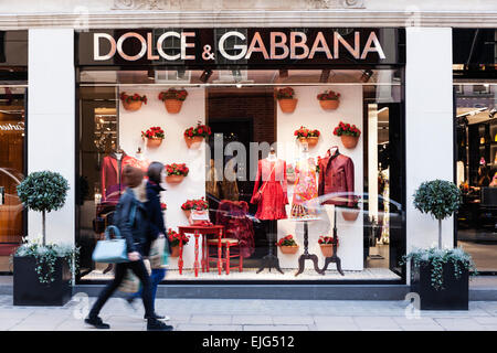 A couple of young women walk by the Dolce & Gabbana  fashion store on Old Bond Street, Mayfair, London, England. - Stock Photo
