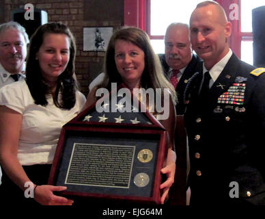 Col. Ralph Kauzlarich, former 1st Infantry Division Strategic Effects Chief, presents a flag to Jessica Bucca-Huges - Stock Photo