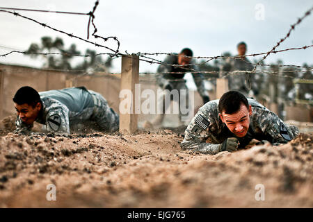 During a team-building challenge, U.S. Army 1st Lt. Alan Roy, right, and Sgt. Luis Garcia crawl through an obstacle - Stock Photo