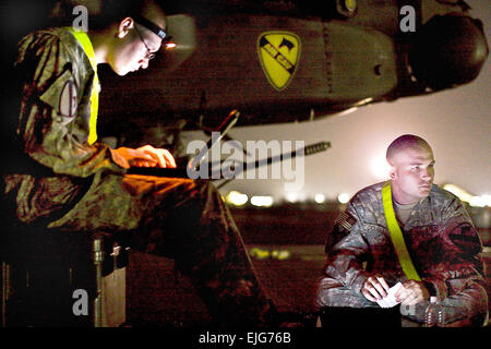 Working under a night sky, U.S. Army Sgt. Derrick Douglas, right, and Spc. Nicholas Kirckof, left, review aircraft - Stock Photo