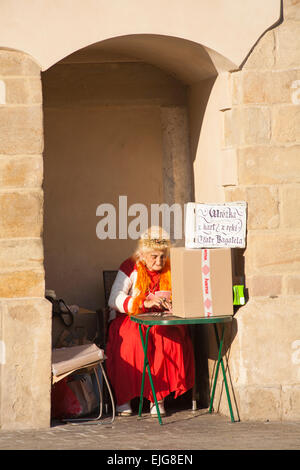 Old woman Fortune Teller card reader at Rynek Glowny, The Main Market Square, Krakow, Poland in September - Stock Photo