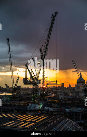 Silhouetted cranes over the Bloomberg Place construction site, London EC4, in the setting sun - Stock Photo