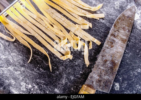 homemade pasta dough is being processed - Stock Photo
