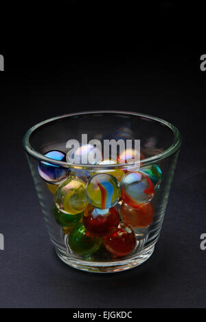 Colored marbles in glass on black background - Stock Photo