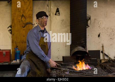 Blacksmith Frank Verga working on a forge in a metal working shop in Charleston, SC - Stock Photo