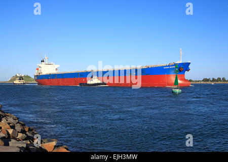 A large cargo ship entering the Hunter River on its way to the Port of Newcastle, NSW, Australia. There are two - Stock Photo