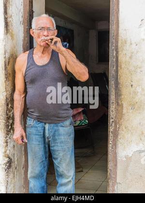 Hispanic Cuban man stands in the doorway of his home smoking cigar - Stock Photo