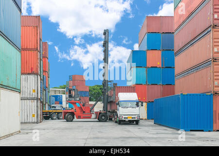 Forklift handling container box loading to truck - Stock Photo