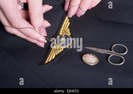 Sewing an airline pilots wings onto a uniform jacket - Stock Photo