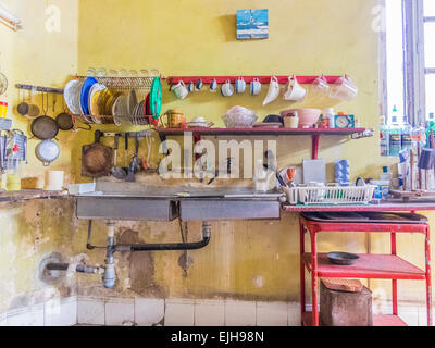 A view of the sink and cups and dishes stored above it in a kitchen of a Cuban home. - Stock Photo