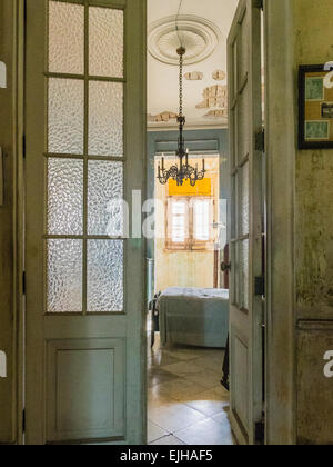 A view through the glass paned doorway to a pre-revolution bedroom with chandelier in an old mansion in Vedado, - Stock Photo