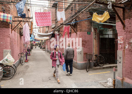 Residents walk through an old residential neighbourhood in downtown Shanghai, China - Stock Photo