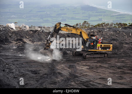 WESTPORT, NEW ZEALAND, MARCH 4, 2015: A digger removes high grade coal from a seam at an open cast coal mine - Stock Photo