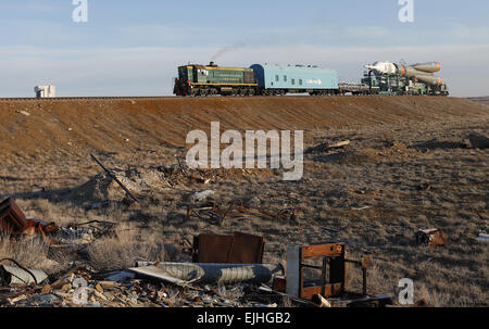 Baikonur, Kazakhstan. 25th Mar, 2015. A Soyuz FG rocket carrying the Soyuz TMA-16M spacecraft being rolled out by - Stock Photo