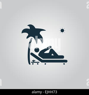 Man relaxing on a deck chair under palm tree - Stock Photo