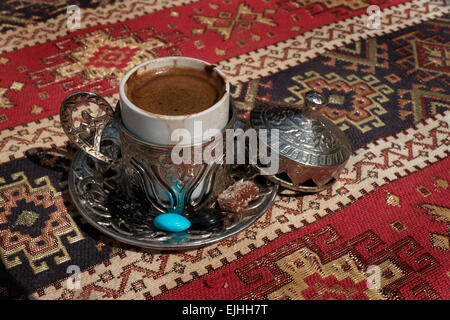 Traditional Turkish coffee in silver cup, with sweets and candies on bar table - Stock Photo
